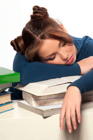 Beautiful girl sleeping on a stack of books, gray background