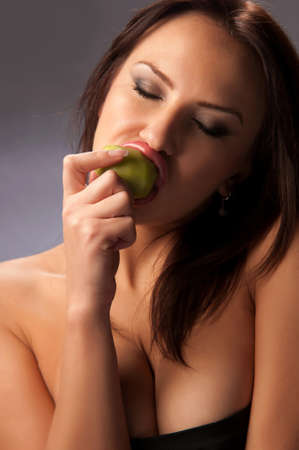 sexually: beautiful young woman sexually eating kiwi on a blue background