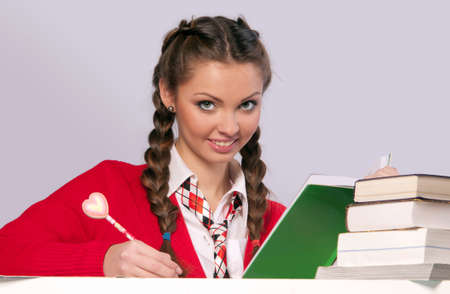 beautiful girl sitting in front of books, gray background photo