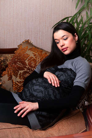 a young pregnant woman in the interior of the apartment near the plant Stock Photo - 13180145