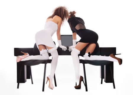 sexy two women at office with a laptop on a white background Stock Photo