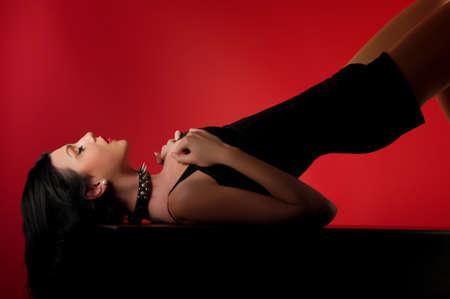 punos: Retrato de la moda joven modelo de mujer hermosa. Las mujeres Glamour con largo cabello negro y peinado sexy. Mujer con collar de cuero con tachuelas en una cadena de metal