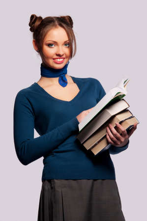 young girl standing with a bunch of books on an isolated background photo