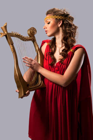 cute girl in a red tunic with a harp