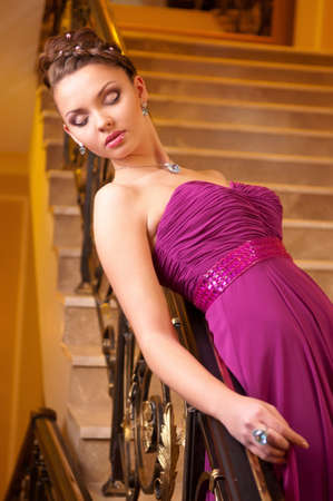 attractive young woman in a beautiful dress sloit on the stairs in the hotel lobby photo