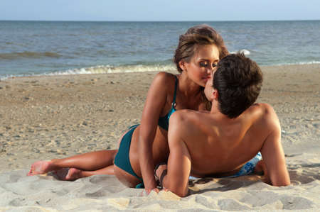 passionate couple: guy kiss his girlfriend on the beach