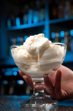 a glass of ice-cream stands on the bar Stock Photo