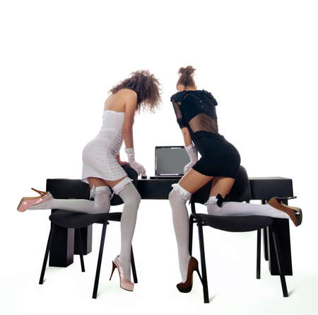 sexy two women at office with a laptop on a white background photo