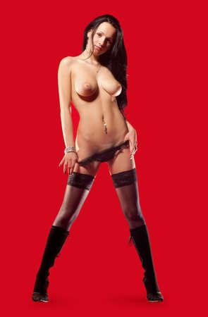 mujer sexy desnuda: sexy mujer desnuda con medias negras sobre un fondo rojo Foto de archivo
