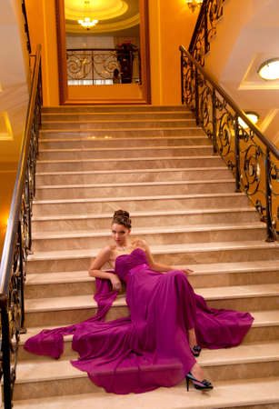 young woman in a long dress lying on the stairs in the hotel lobby