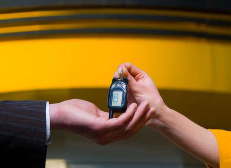 auto mechanic: Young saleswoman handing a car key to a customer  Stock Photo