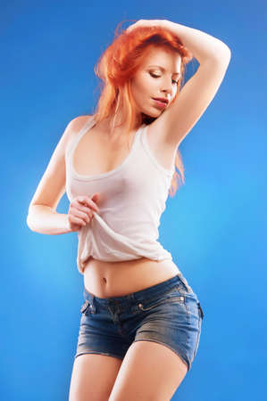 women breast: woman with red hair on a blue background Stock Photo