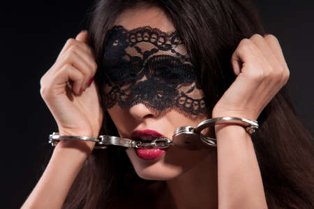 woman in a black mask and metal handcuffs on a dark background photo