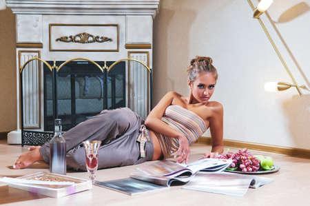 indoor shot: mujer sentada y leyendo la revista tiro cubierta