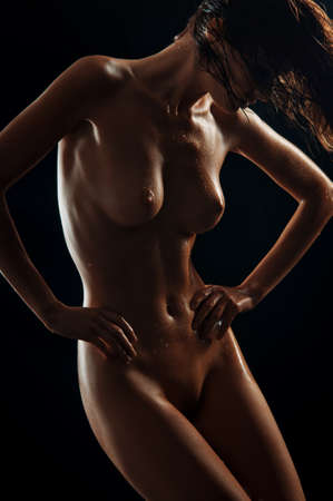 Beautiful young naked woman isolated on black