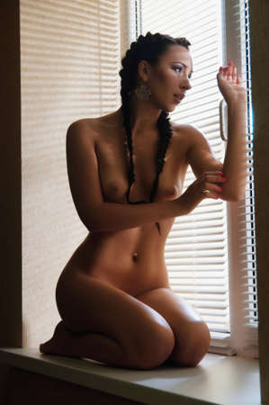 beautiful naked young woman on the window sill venetian blind Stock Photo - 14680297