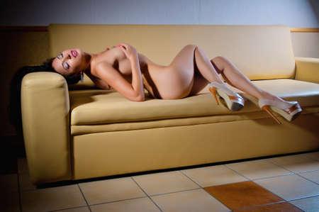 femme se deshabille: portrait d'une jeune fille nue sexuelle magnifique sur le canap� Banque d'images