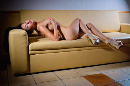 undressed young: sexual portrait of beautiful bare girl on sofa Stock Photo