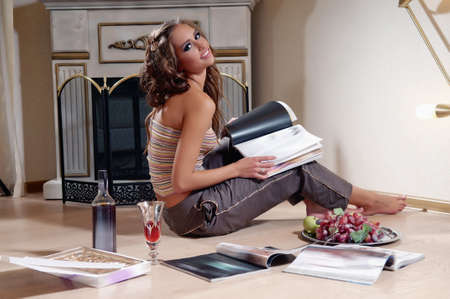 young woman sitting and reading magazine indoor shot Stock Photo - 14718705