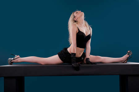 Pretty flexible dancer woman sit on twine and stretching on a blue background Stock Photo - 14722120
