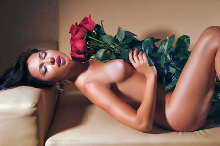 portrait of a sexy girl with red roses on a beige couch