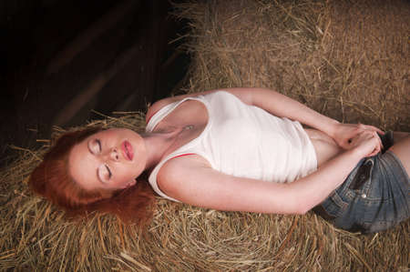 woman with red hair lying on a haystack photo