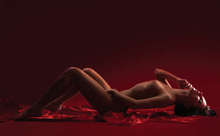 beautiful nude young woman on a red background Stock Photo - 14937899