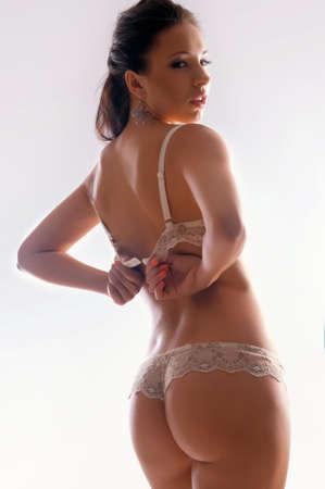 mujeres negras desnudas: Hermosa morena quita un sost�n sobre fondo blanco