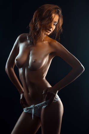 naked belly: nude woman with a beautiful figure on a dark background in the studio
