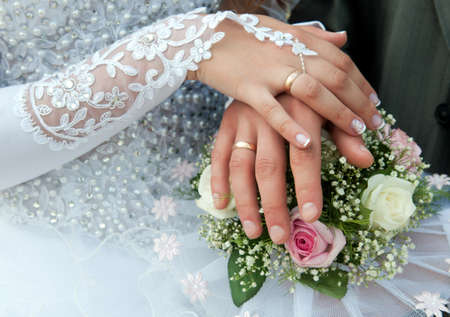 Hands of groom and bride with wedding rings on top of the brides bouquet