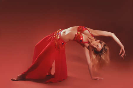 Attractive girl dances east dance isolated on a red background photo