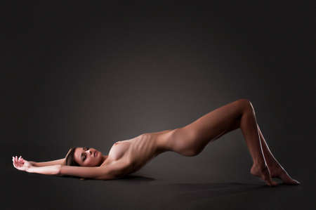 naked youth: woman with a beautiful figure on a dark background in the studio