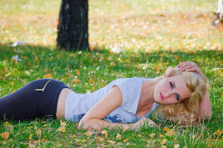 Beautiful blond girl lying on autumn leaves photo