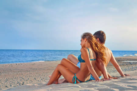 sexy couple on beach: picture of happy couple sitting on the beach Stock Photo