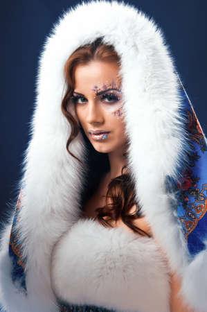 Winter girl with white fur hat wearing warm fur coat Standard-Bild