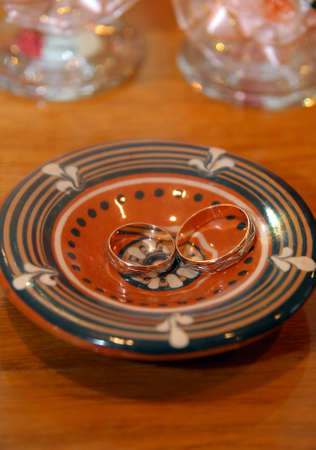 Two Wedding rings lying on special ceramic saucer photo