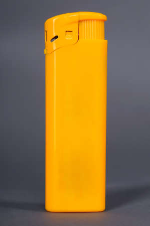 Isolated yellow plastic lighter against the gray background photo