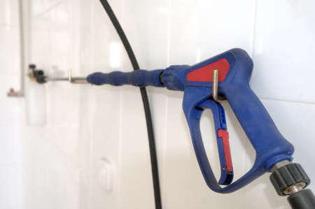 Water spray gun for car washing on a white wall photo