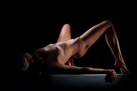 naked woman with a beautiful figure on a dark background in the studio Stock Photo