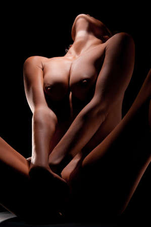 naked belly: naked woman with a beautiful figure on a dark background in the studio Stock Photo