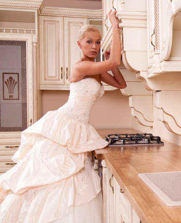 beautiful bride stands in the kitchen and laughs