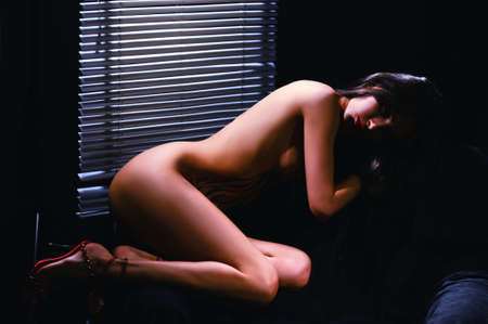 topless young girl stand before venetian blind in dark Stock Photo - 17444802