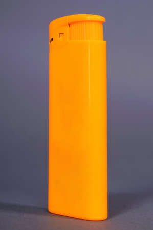 Isolated yellow plastic lighter against the gray background Stock Photo - 17538442