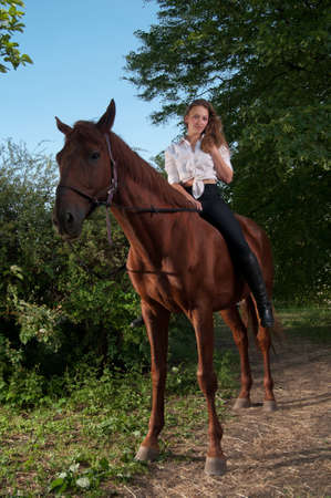 Beautiful young woman riding chestnut horse photo