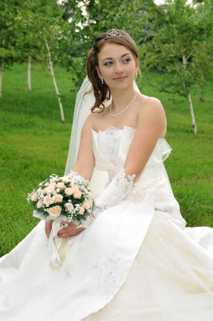 Happy bride in park with bouquet of flowers photo