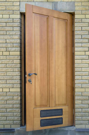 brown wooden door of a house entrance with an brick front Stock Photo - 17565352