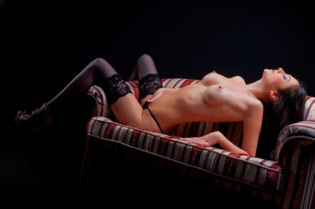 vrijen: mooie sexy naakte brunette op de bank Stockfoto
