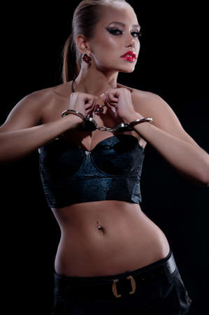 Beautiful girl in metal handcuffs on a black background photo