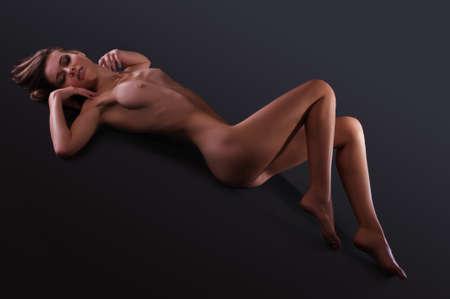 naked young women: Обнаженная женщина с красивой фигурой на темном фоне в студии