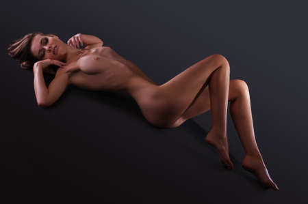 joven desnudo: mujer desnuda con una hermosa figura sobre un fondo oscuro en el estudio